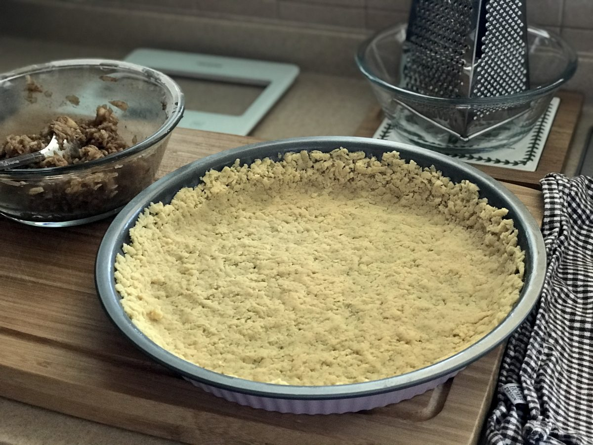 Křehký koláč s philadelphií a jablky utlačení strouhaného těsta ve formě